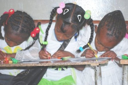Ethiopian girls dressed for a party and colouring a Manna picture